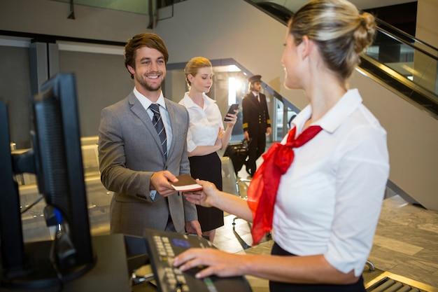Empresario dando su tarjeta de embarque al personal femenino en el mostrador de facturación Foto gratis
