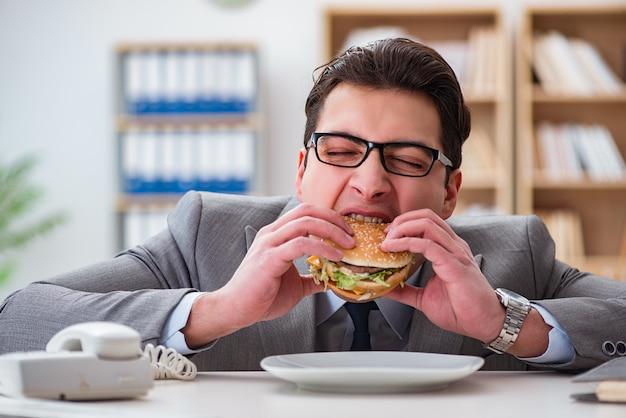 Empresario divertido hambriento comiendo sandwich de comida chatarra Foto Premium