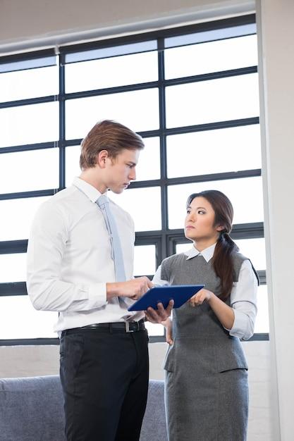 Empresario y empresaria interactuando con tableta digital en la oficina Foto Premium