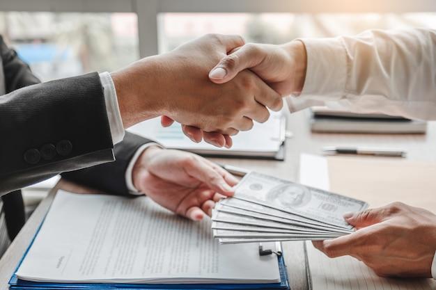 Empresario estrecharme la mano dando sobornos de corrupción de billetes de dólar al gerente comercial para tratar el contrato Foto Premium