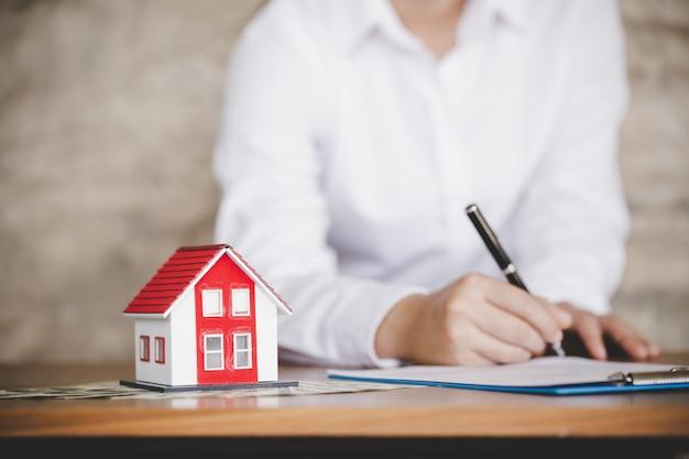 Empresario firma contrato detrás de casa modelo arquitectónico Foto Premium