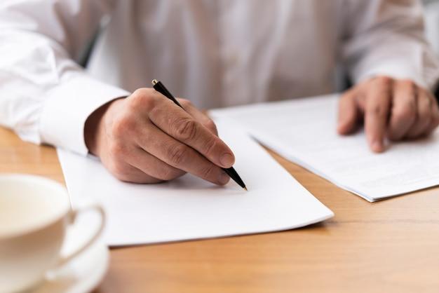 Empresario firmando papeles en la oficina Foto gratis
