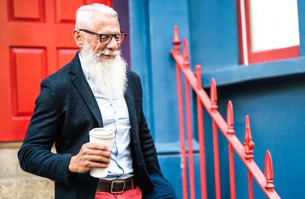 Empresario hipster caminando con una taza de café para llevar Foto Premium