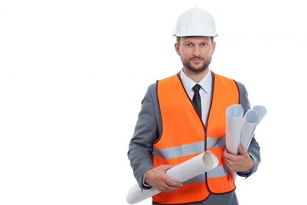 Empresario ingeniero sosteniendo planos del plan de construcción posando en blanco con casco y chaleco de seguridad naranja Foto gratis