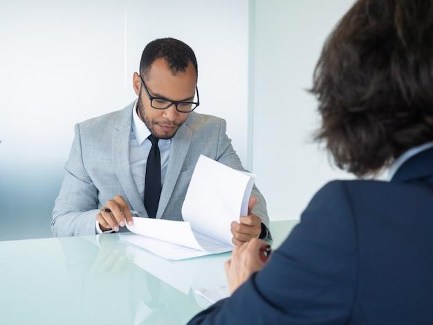 Empresario leyendo contrato durante la reunión Foto gratis