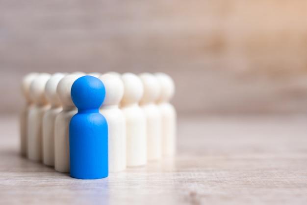 Empresario líder azul con multitud de hombres de madera. concepto de liderazgo, negocios, equipo, trabajo en equipo y gestión de recursos humanos Foto Premium