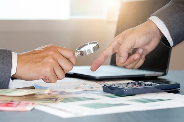 Empresario con lupa para análisis de datos financieros Foto Premium