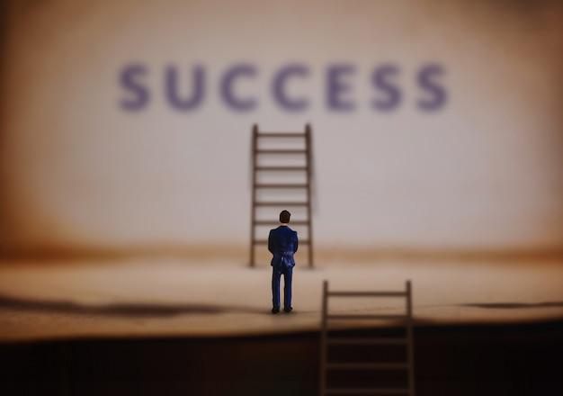 Empresario en miniatura con escalera de escalera de éxito Foto Premium