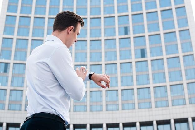 Empresario mirando el reloj cerca del edificio | Descargar