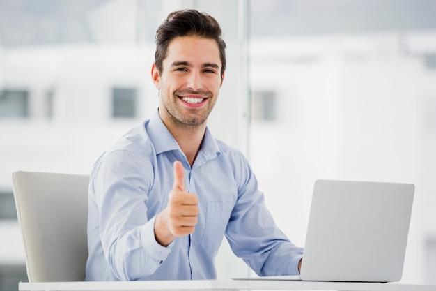 Empresario mostrando los pulgares hacia arriba mientras usa la computadora portátil Foto Premium