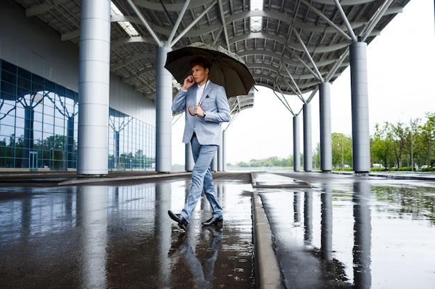 Empresario pelirrojo con paraguas hablando por teléfono Foto gratis