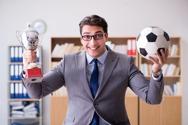 Empresario con pelota de futbol en la oficina Foto Premium