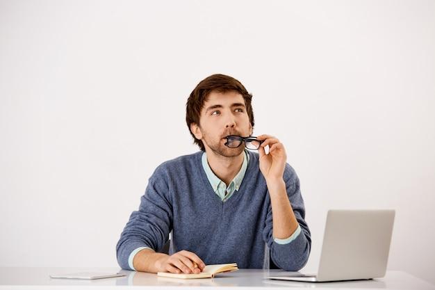 Empresario pensativo sentado en el escritorio de la oficina, mordiendo el borde de las gafas, mirando hacia arriba pensando, buscando inspiración como escribir en el cuaderno Foto gratis
