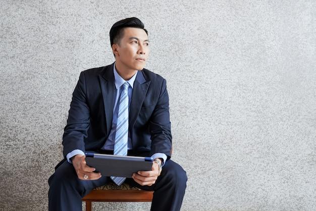 Empresario pensativo con tableta Foto gratis