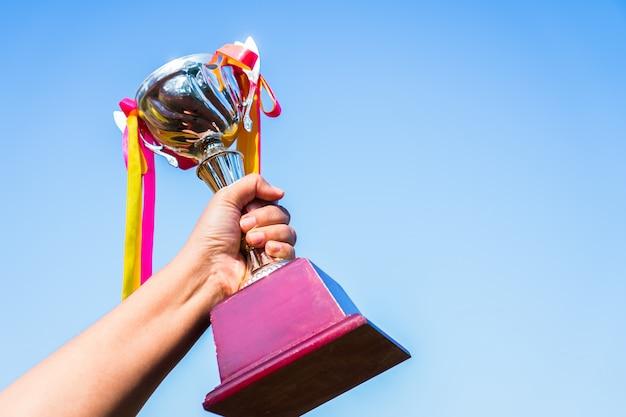 Empresario con premio trofeo de oro con cinta muestra victoria para el mejor premio de logro de éxito de negocios Foto Premium