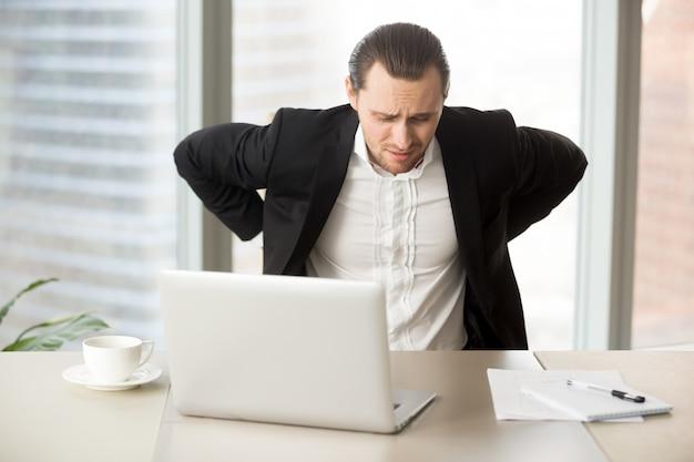 Empresario que sufre de dolor de espalda en el lugar de trabajo Foto gratis