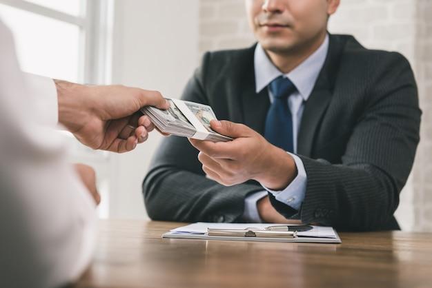 Empresario recibiendo dinero después de la firma del contrato Foto Premium