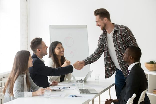 Empresario sonriente que da la bienvenida a un nuevo socio en una reunión de grupo con un apretón de manos