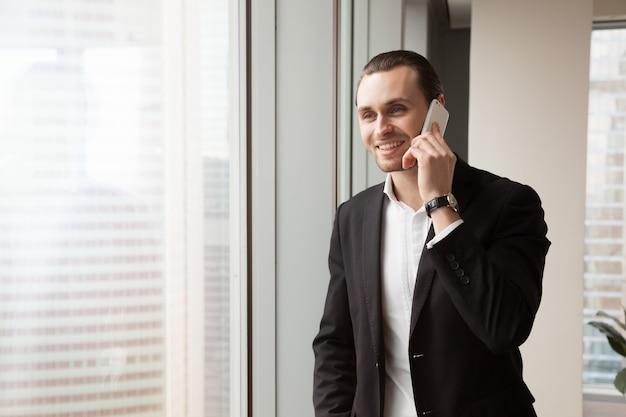 Empresario sonriente responde a la llamada en oficina Foto gratis