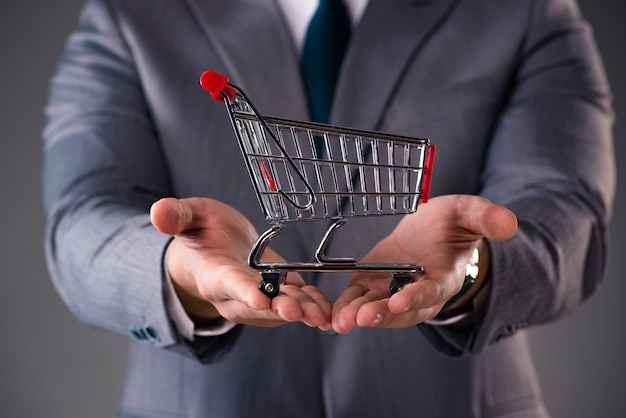 Empresario sosteniendo carrito de compras en concepto de negocio Foto Premium