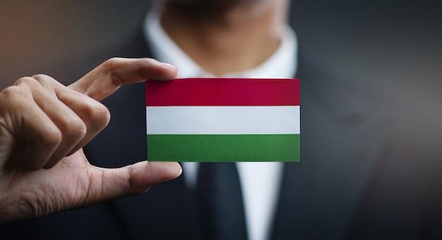 Empresario sosteniendo la tarjeta de bandera de hungría Foto Premium