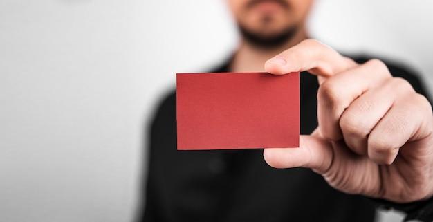 Empresario sosteniendo una tarjeta de visita vacía roja Foto gratis