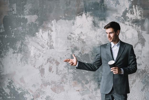Empresario sosteniendo una taza de café para llevar haciendo un gesto con la mano contra una pared grunge Foto gratis