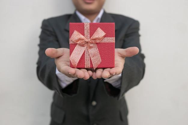 Empresario sostiene la caja de regalo Foto Premium