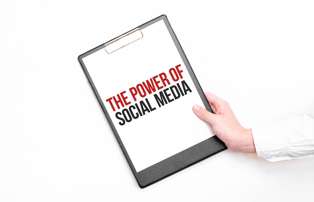 Un empresario sostiene una carpeta con una hoja de papel con el texto el poder de las redes sociales. concepto de negocio. Foto Premium