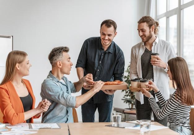 Empresarios en el almuerzo comiendo pizza Foto gratis