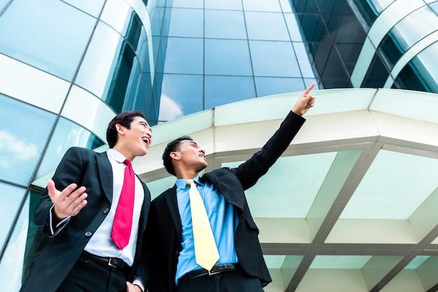 Empresarios asiáticos frente a edificio de gran altura Foto Premium