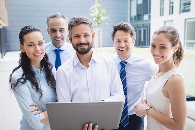 Empresarios confiados de pie fuera del edificio de oficinas con laptop Foto gratis