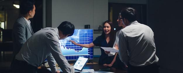 Empresarios y empresarias de asia que se reúnen ideas de lluvia de ideas que conducen a colegas del proyecto de presentación de negocios que trabajan juntos planean la estrategia de éxito disfrutan del trabajo en equipo en una pequeña oficina nocturna moderna Foto gratis