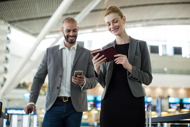 Los empresarios esperando en la cola en un mostrador de facturación con equipaje Foto gratis
