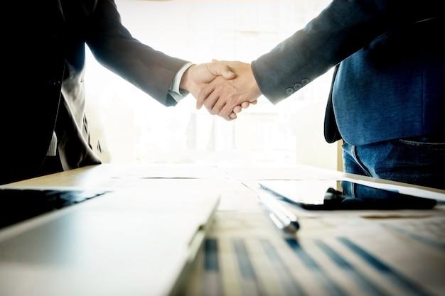 Empresarios estrechar la mano durante una reunión Foto gratis
