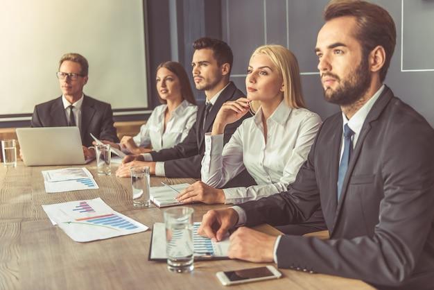 Los empresarios exitosos con ropa formal están escuchando. Foto Premium
