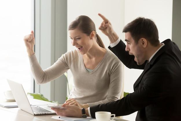Empresarios felices celebrando el éxito del negocio en línea Foto gratis