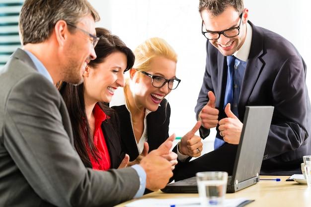 Empresarios mirando portátil con éxito Foto Premium