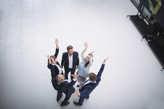 Empresarios de pie con las manos levantadas Foto gratis