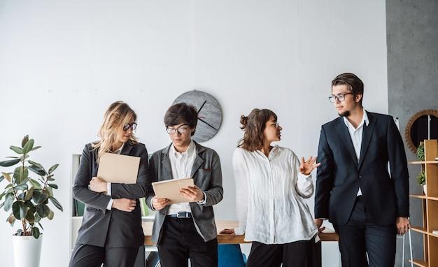 Los empresarios de pie en la oficina discuten Foto gratis