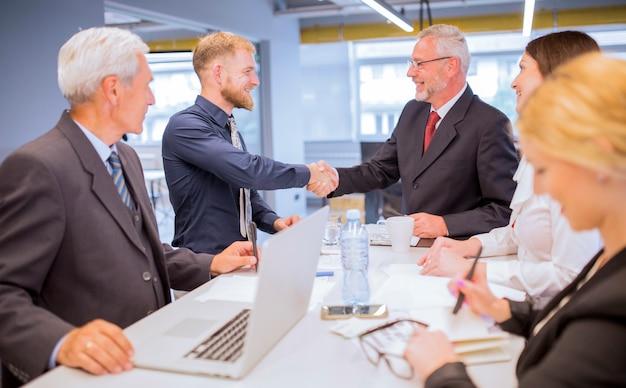 Empresarios que miran a dos hombres de negocios que sacuden las manos en la reunión de negocios Foto gratis