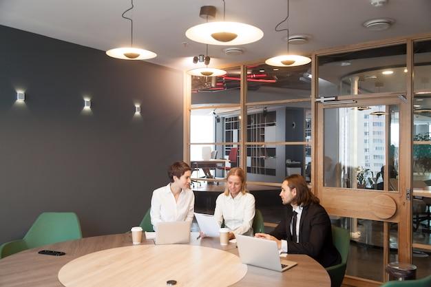 Empresarios que tienen discusión en la reunión del equipo en el interior moderno de la oficina Foto gratis