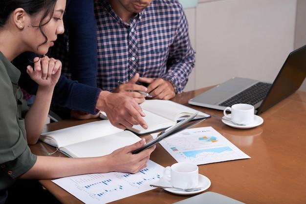 Empresarios recortados discutiendo gráficos y diagramas en la oficina Foto gratis