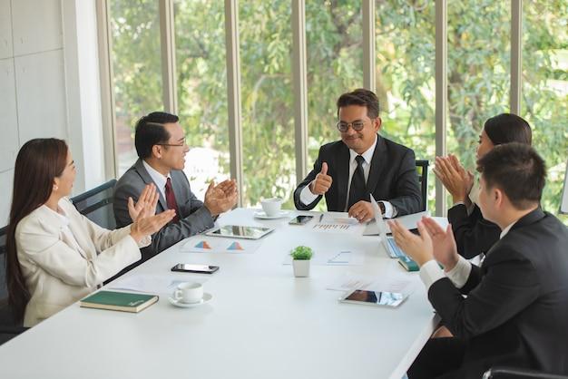 Empresarios reunidos en la mesa de la oficina con el disfrute. Foto Premium