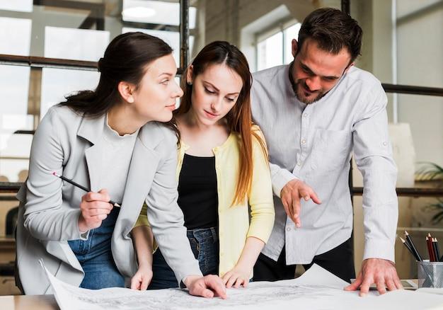 Empresarios trabajando en el plano azul en el lugar de trabajo Foto gratis