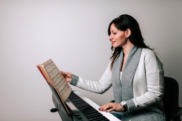 Encantador músico practicando piano clásico tocando partituras Foto Premium