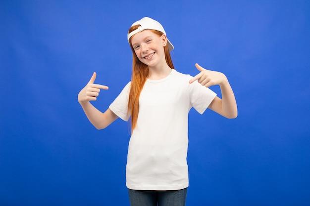 Encantadora chica adolescente pelirroja en una camiseta blanca con una maqueta estampada azul Foto Premium