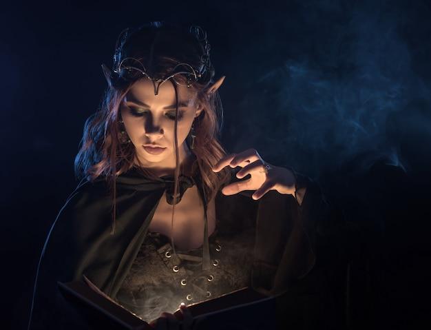 Encantadora chica en capa esmeralda practicando habilidad mágica. Foto Premium