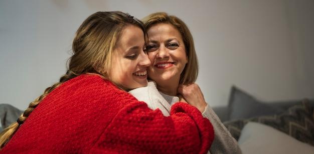 Encantadora hija y madre abrazando Foto gratis