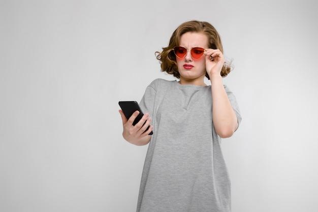 Encantadora joven en una camiseta gris un gris. chica de gafas rojas con teléfono Foto Premium
